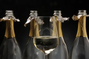 a glass of champagne and four bottles of champagne